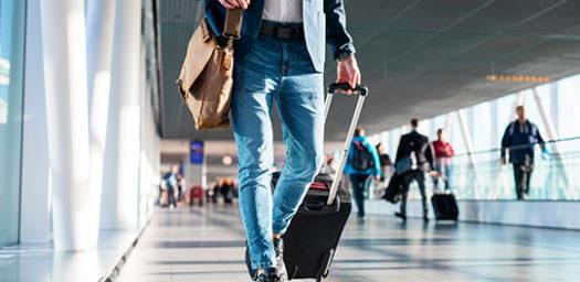 Viajero con maleta caminando por el aeropuerto