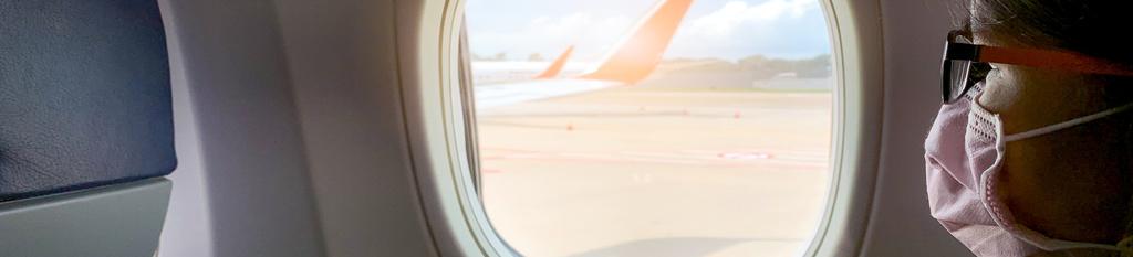 Mujer con mascarilla en avión