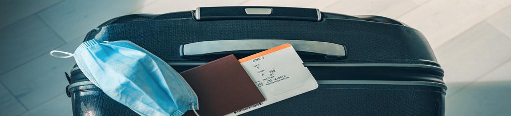 Maleta en aeropuerto con billete de avión y mascarilla