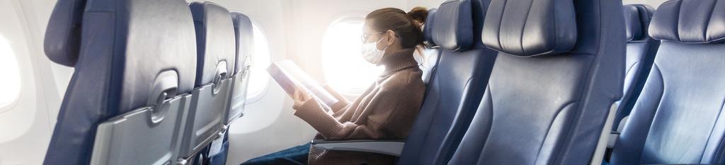 Mujer con mascarilla en el interior de un avión