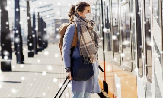 Mujer con mascarilla esperando para acceder a un tren